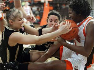 Bowling Green forward Alexis Rogers (32), right, battles Purdue guards Brittany Rayburn (5) and Courtney Moses (15) for a loose ball.