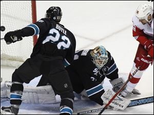 San Jose Sharks' Dan Boyle, left, watches a goal by Detroit Red Wings' Niklas Kronwall, during the first period of an NHL hockey game in San Jose, Calif. At center is Sharks goalie Antti Niemi; and Red Wings' Tomas Homstrom is at right.