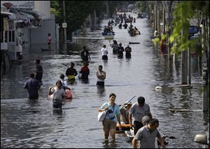 Thai residents carry their belongings through flood waters in October as they move to higher ground at Bangkok's Don Muang district, Thailand.