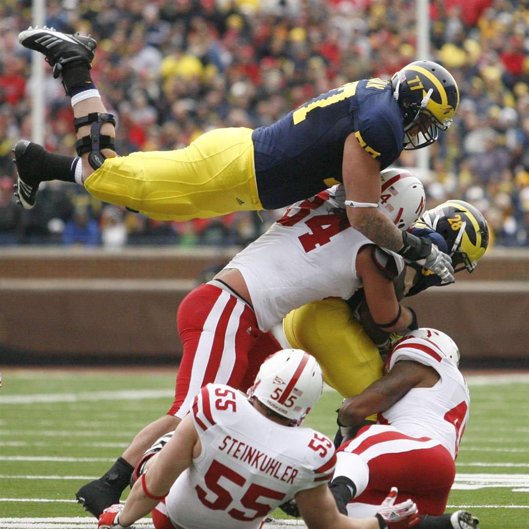 Michigan-s-Taylor-Lewan-leaps-over-a-pile
