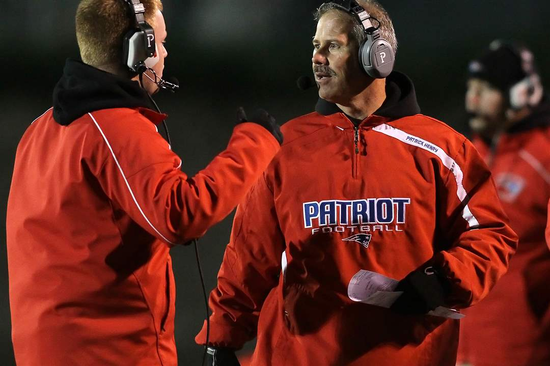 Patrick-Henry-head-coach-Bill-Inselmann-confers-with-his-assistants