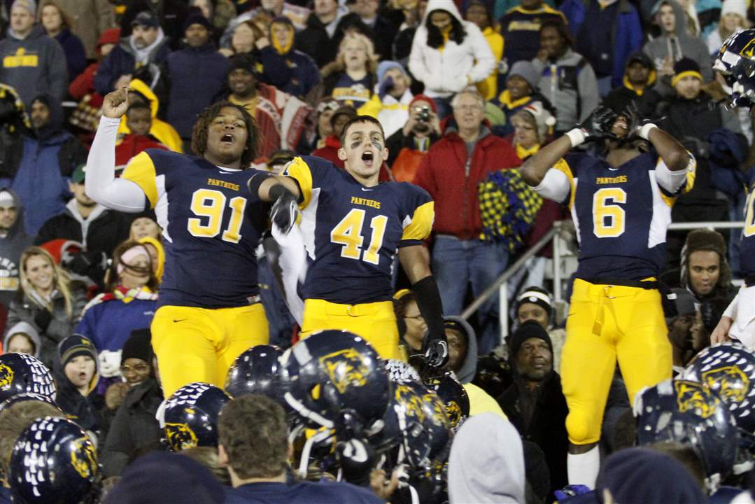 Whitmer-players-Marquise-Moore-91-Alonza-Lucas-6-and-Bryce-Larkin-41-join-fans-in-celebration