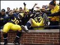 University of Michigan players Thomas Rawls, 38, and Frank Clark, 57, celebrate with fans after the Wolverines defeated the Nebraska Cornhuskers at the Big House, Saturday.