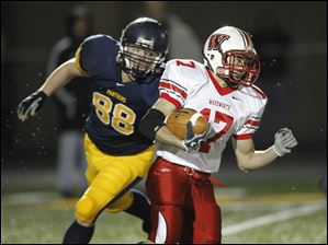 Wadsworth's Nate Winkler, 17, is pursued by Whitmer's Nick LaPoint as he returns a kickoff during a Division I state playoff football game in Sandusky, Ohio.