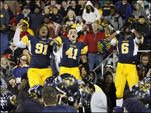 Whitmer  players Marquise Moore, 91, Bryce Larkin, 41, and Alonzo Lucas, 6, celebrate with fans after they beat Wadsworth in a Division I regional championship playoff playoff football game in Sandusky.