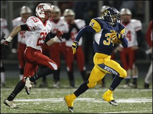 Whitmer's Jody Webb, 34, runs for a touchdown as  Wadsworth's Chester Foth, 29, pursues, during a Division I state playoff football game in Sandusky.