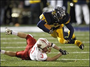 Whitmer's Jody Webb, 34, is airborne after being tripped up by Wadsworth's Anthony Pappas, 3,  during a Division I state playoff football game in Sandusky.