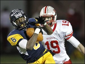 Whitmer's Alonzo Lucas, 6, hauls in a pass for a touchdown in front of Wadsworth's Jon Kuss, 19,  during a Division I state playoff football game in Sandusky, Ohio, Saturday.