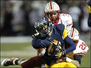 Whitmer's Jody Webb, 34, runs for a first down as Wadsworth's Charles Edwards, 28, tackles him during a Division I state playoff football game in Sandusky, Ohio, Saturday.
