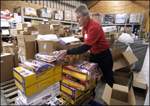 Bob Osborn unpacks toys at the Meijer in Rossford, where groups of inventory are set aside for Black Friday selling.