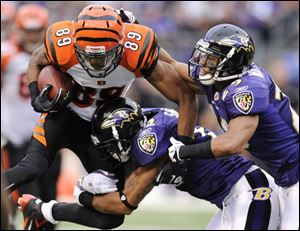 Cincinnati Bengals wide receiver Jerome Simpson (89) is tackled by Baltimore Ravens defenders Jimmy Smith, center, and Cary Williams in the second half in Baltimore, Sunday. Baltimore won 31-24.
