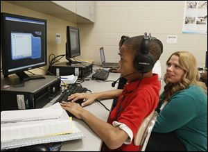 Robinson teacher Tamra Bacon observes seventh-grader Randy martin's progress as he reads on a computer.