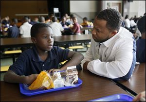 Marquan Whittaker, a third grader at Robinson Elementary, pauses in the school cafeteria to listen to the advice of Lawrence D. Tribble, Jr., a member of the Village 50 volunteers who help before and during school.