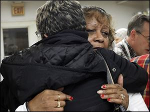 Henrietta Armstrong, head cook of MLK Kitchen for the Poor and sister of long-time executive director Juanita Person who passed away this year, receives a hug during Thanksgiving lunch. The family is determined to keep the charity going and to feed the area's hungry people.