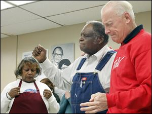 Former Toledo Mayor Carty Finkbeiner, right, joins Henrietta Armstrong, left, and Leonard Mosley in prayer.