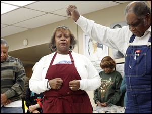 Harvey Savage Jr., from left, Henrietta Armstrong, and Brother Leonard Mosley  pray before Thanksgiving lunch at MLK Kitchen for the Poor.