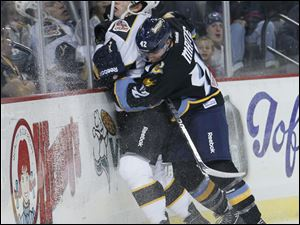 Toledo Walleye player Brian Matte, 42, slams Cincinnati Cyclones player Maury Edwards, 6, into the boards during the first period, Friday, November 25, 2011.