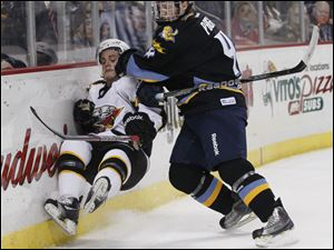 Walleye player Kyle Page, 4, flattens Cincinnati Cyclones player Anthony Luciani, 26, during the second period.