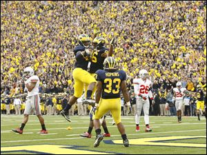 Michigan's Junior Hemingway (21), Kevin Koger (86) and Stephen Hopkins (33) celebrate Hemingway's touchdown in the first quarter against Ohio State at the Big House Saturday.