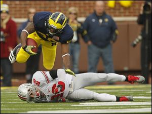 Michigan's Kevin Koger (86) is upended by Ohio State's Tyler Moeller (26) after picking up a first down in the second quarter. Koger, a Whitmer graduate, hauled in four passes for 40 yards and a touchdown.