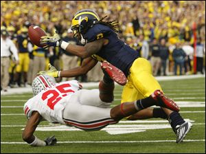 Michigan's player Martavious Odoms (9) bobbles the ball but makes the catch against Ohio State defender Bradley Roby (25).