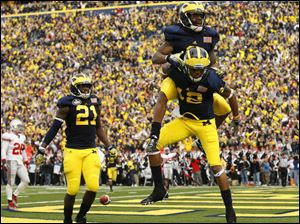 Michigan's Martavious Odoms (9) and Roy Roundtree (12) celebrate Odoms third quarter touchdown. The score put the Wolverines up 30-24 over the rival Buckeyes.