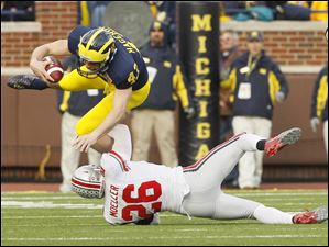 Michigan punter Will Hagerup (43) is tackled by Ohio State's Tyler Moeller (26) after fumbling the snap during the third quarter.