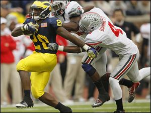 Michigan's Fitzgerald Toussaint (28) is tackled by Ohio State'sTaylor Graham (19) and C.J. Barnett (4) during the fourth quarter.