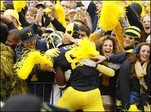 Michigan's Kevin Koger, a senior, celebrates with fans after the Wolverines defeated Ohio State in his final game at the Big House.