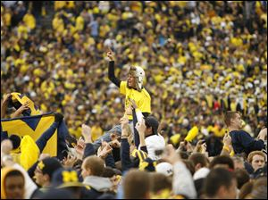 Michigan students and fans rush the field after the Wolverines defeated the rival Buckeyes Saturday at the Big House.