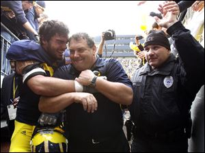 Michigan coach Brady Hoke gets a hug from player Craig Roh after the Wolverines defeated the Ohio State. The Wolverines finished the season 10-2, 6-2 in Hoke's first season at Michigan.