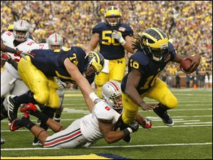 Michigan's Denard Robinson dives into the end zone despite the efforts of Ohio State defender Etienne Sabino, 6, during the second quarter.