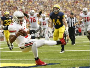 Ohio State quarterback Braxton Miller (5) spins into the end zone for a second quarter touchdown at the Big House. The freshman quarterback rushed 16 times for 100 yards and another touchdown.