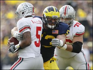 Michigan's Ryan Van Bergen (53) tries to wrap up Ohio State's Braxton Miller (5) after beating J.B. Shugarts (76) in the first quarter at the Big House Saturday.