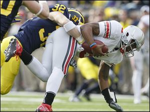 Michigan's Jordan Kovacs (32), a Clay alumnus, sacks Ohio State quarterback Braxton Miller (5) during the first quarter at the Big House Saturday.