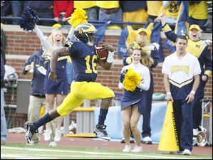 Michigan quarterback Denard Robinson (16) races for a touchdown in the first quarter against Ohio State at the Big House Saturday.