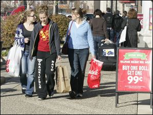 Kayla Fackler, 20, her sister Dayna Fackler, 15, and their mom Dee Fackler, of McClure, carry their purchases at Fallen