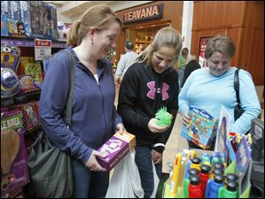 Leslie Conrad, Lauren Reichel, and her mom Andrea Reichel, of Onsted, Mich., shop at Go! Games inside Westfield Franklin Park Mall.