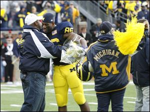 Michigan's Kevin Koger, a Whitmer alumnus, hugs his father, Carl, as his mother Pat waves a flag as he and other seniors are honored before playing Ohio State University at the Big House Saturday.