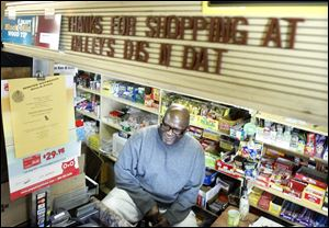 Alfred Dailey, owner of Dailey's Dis N Dat , sits behind the counter of his convenience store chatting with customers.
