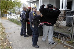 Officer Aaron Riter, left, and Sgt. Rick Moreno, right, with the Toledo Gang Task Force, search two members of the gang called 'Lil Head' on Fernwood Ave. in front of the house where Justin Smith was killed last month.
