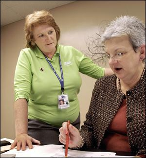 Glenda Plunkett, left, confers with her boss Marilyn Sears, CEO of Shelby Memorial Hospital, in Shelbyville, Ill. Plunkett lost her 11-year American Red Cross job during the recent major overhaul by the Red Cross that cut more than 1,500 jobs and merged many chapters.