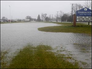 An exterior shot of the Timberstone Junior High sign that is near flood water on Tuesday.