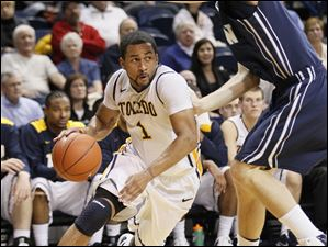 Toledo's Dominique Buckley (1) drives inside against UNC-Wilmington's KK Simmons (14).