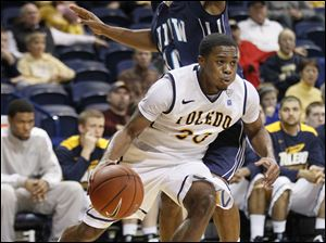 University of Toledo player Julius Brown (20) drives around UNC-Wilmington's Freddie Jackson (10) during the second half.