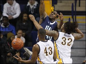UT's Matt Smith (43) and Reese Holliday (32) can't stop UNC-Wilmington's Cedrick Williams (40) as he dunks during the first half.