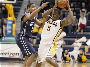 Toledo's Rian Pearson (5) keeps the ball away from UNC-Wilmington player Donte Morales (1).