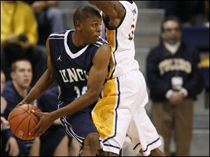 The Rockets' Rian Pearson (5) pressures UNC-Wilmington's Freddie Jackson (10).
