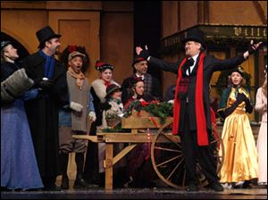 Paul Causman as Scrooge, front right, celebrates the joy of Christmas with his nephew, Fred, second from left, played by Zach Lahey, and townspeople. The Rep production features 130 actors and singers from northwest Ohio and southeast Michigan.