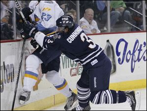 Toledo Walleye player Byron Froese (23) is hit by Greenville Road Warriors player Wes Cunningham (3) during the first period at Huntington Center, Friday.